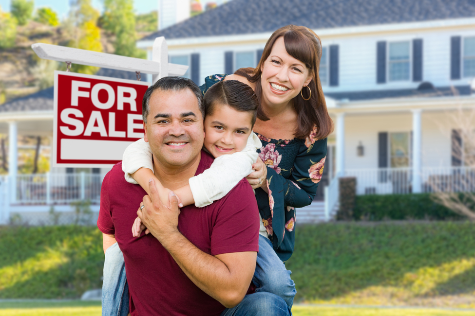 Happy Mixed Race Family In Front of House and For Sale Real Estate Sign.